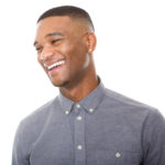 Close up portrait of a handsome young black man laughing on isolated white background